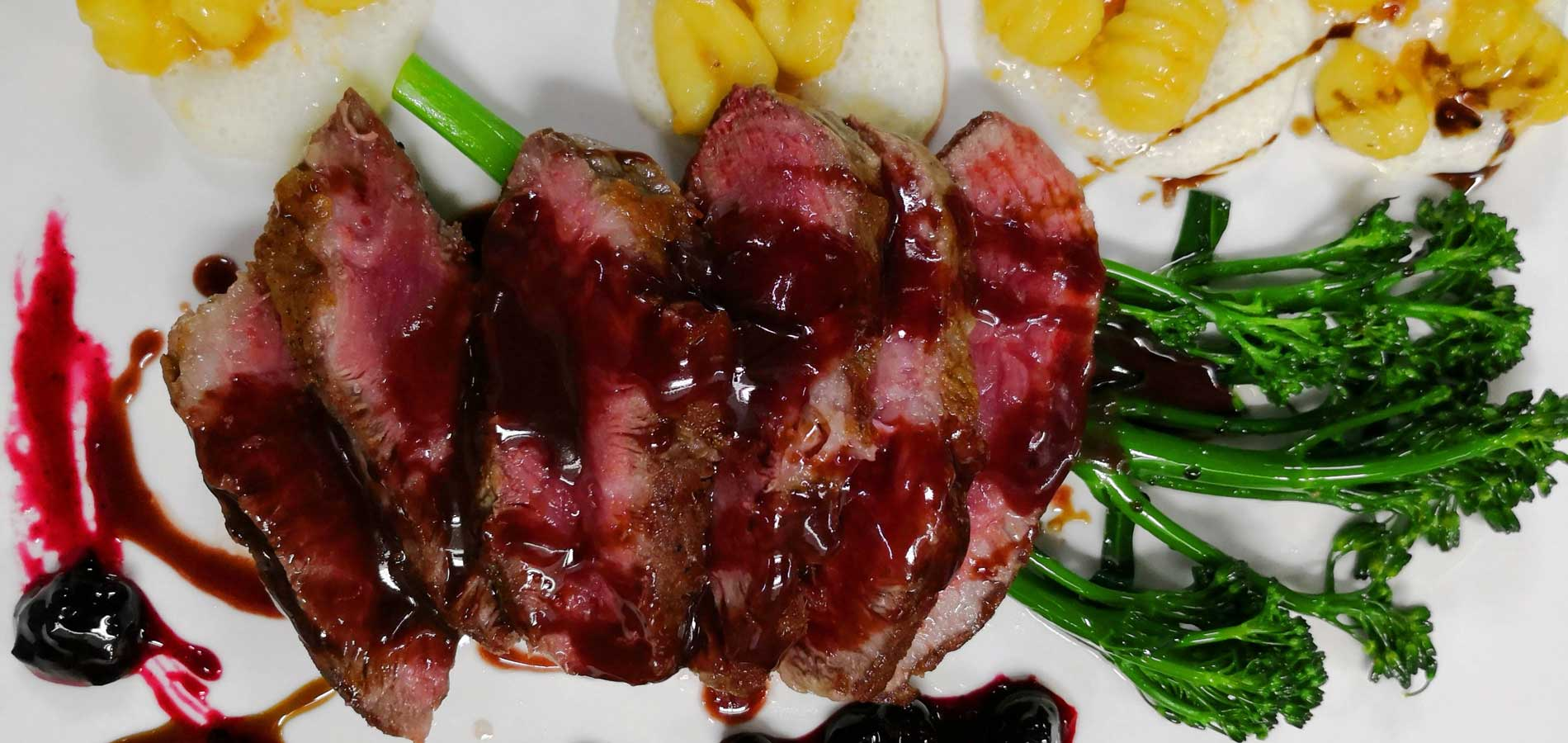 Carnes - Presa Ibérica, ñoquis sobre puré, salsa de frutas rojas y bimi